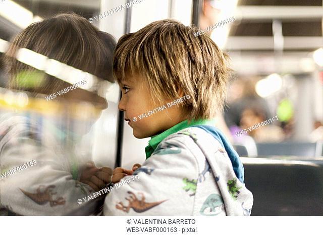 Little boy looking through window of a subway train