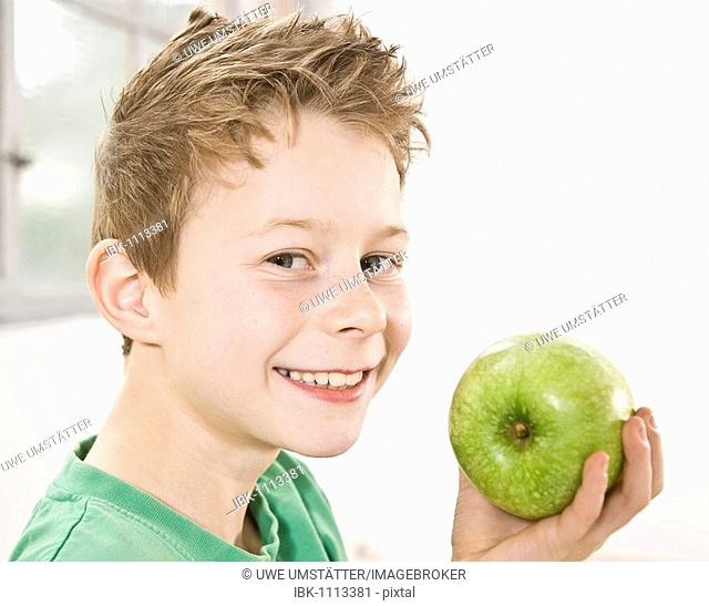 Boy smiling while holding a green apple in front of his face