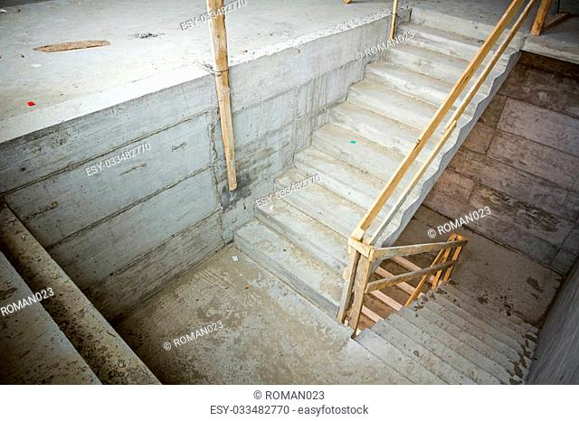 New concrete staircase with temporary wooden handrail, under construction