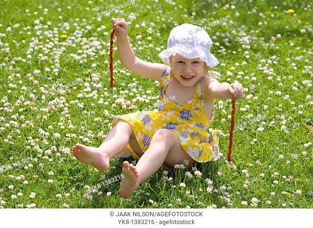 Three Year Old Girl Sitting on Grass, Strawberries on a Grasstraw