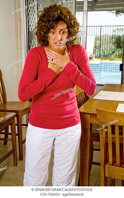 A hypocondriac winces in imagined pain in her kitchen in Mission Viejo, CA, USA