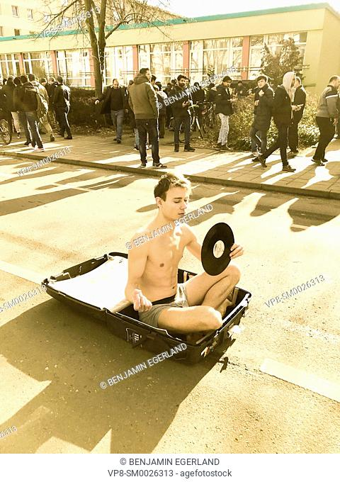 young man in underwear holding old retro phonograph record, nostalgia, sitting in travel suitcase in the middle of the street in public next to passersby
