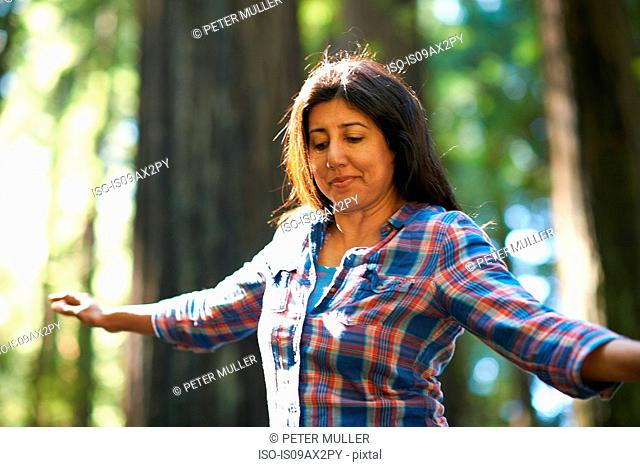 Woman balance walking in forest
