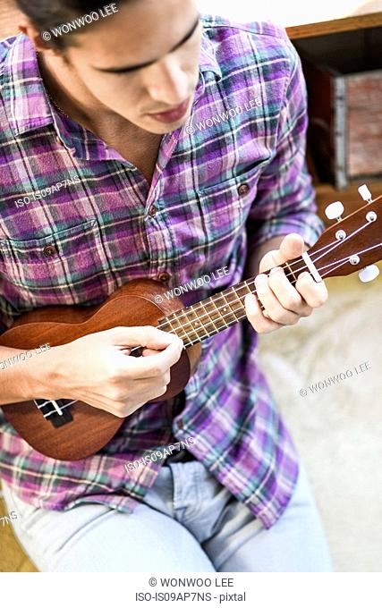 Young man playing ukulele, elevated view