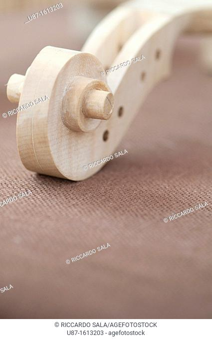 Italy, Lombardy, Cremona, Violin Maker Worshop, Close up of Violin Scrolls Unvarnished