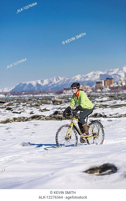 A young woman riding her bicycle on ice and snow next to the Tony Knowles Coastal Trail, Anchorage, Southcentral Alaska, USA