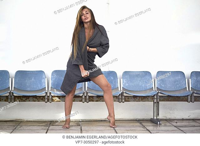sexy woman giving bedroom look, feeling attractive, in front of row of blue chairs. Russian ethnicity. In holiday destination Hersonissos, Crete, Greece