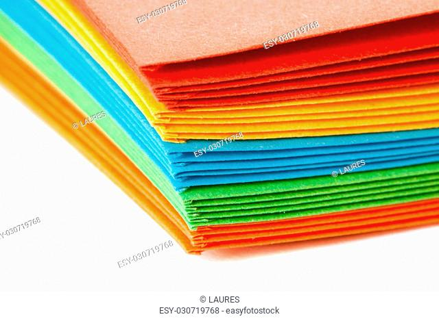 A stack of bright colored paper envelopes