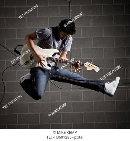 Man jumping in air while playing guitar