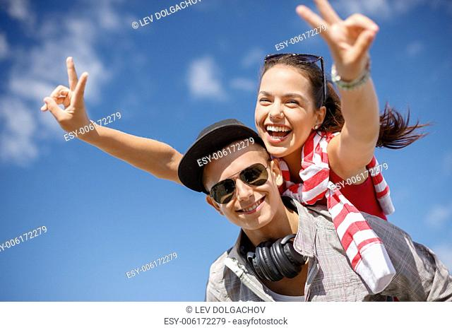 summer holidays, relationships and teenage concept - smiling teenagers in sunglasses having fun outside and showing v-sign