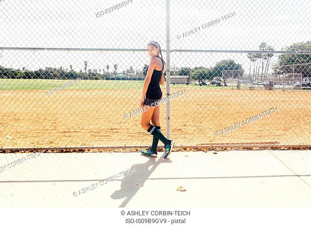 Portrait of schoolgirl soccer player at wire fence on school sports field