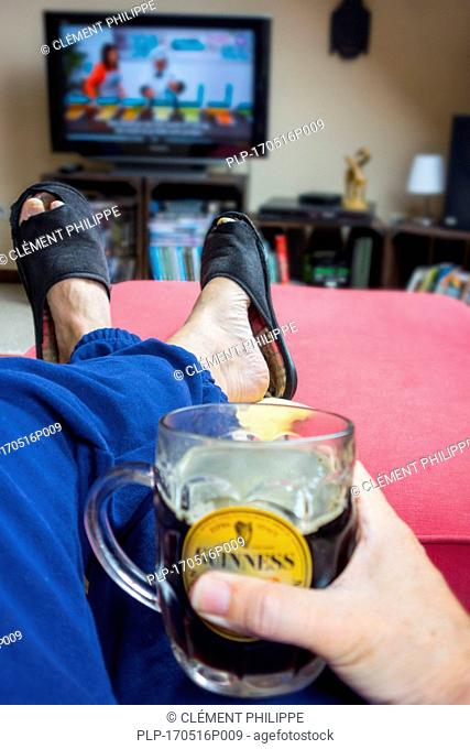 Couch potato, lazy man in comfy chair with pint of beer wearing worn slippers with big toes sticking through and watching television in living room