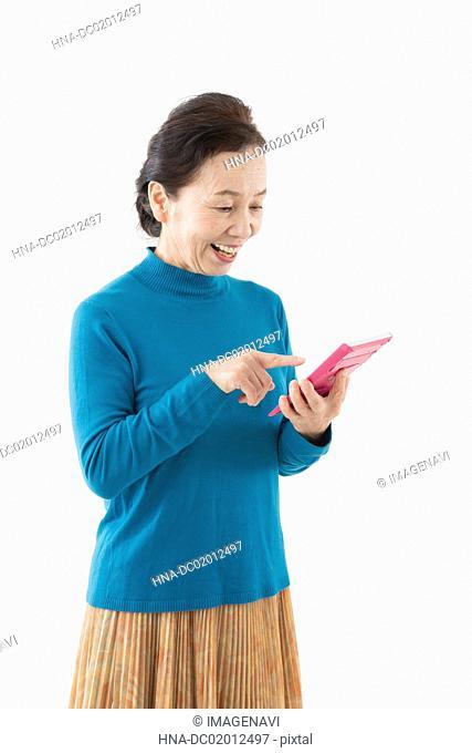 Senior woman having calculator