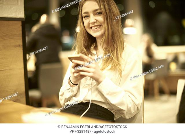 smiling young woman using smartphone indoors in café, charge cable plugged in, in Cottbus, Brandenburg, Germany