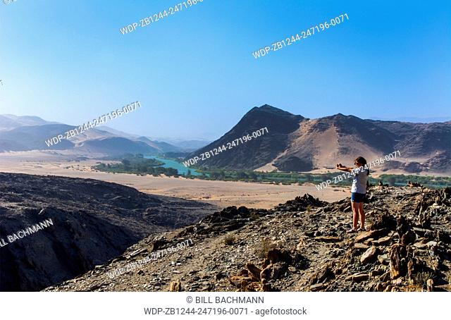 Namibia Northern Desert of Namib Desertgreen tourist taking pictures of oasis river valley sand dunes of Hartmann Berge deserted land Hartmann Valley Marienflub...