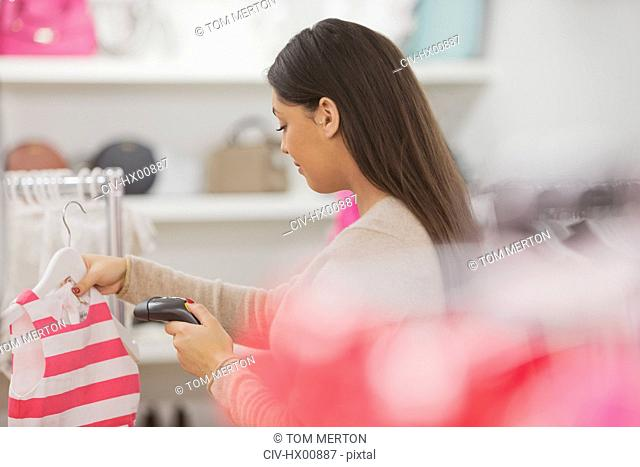 Clothing shop owner scanning clothing doing inventory