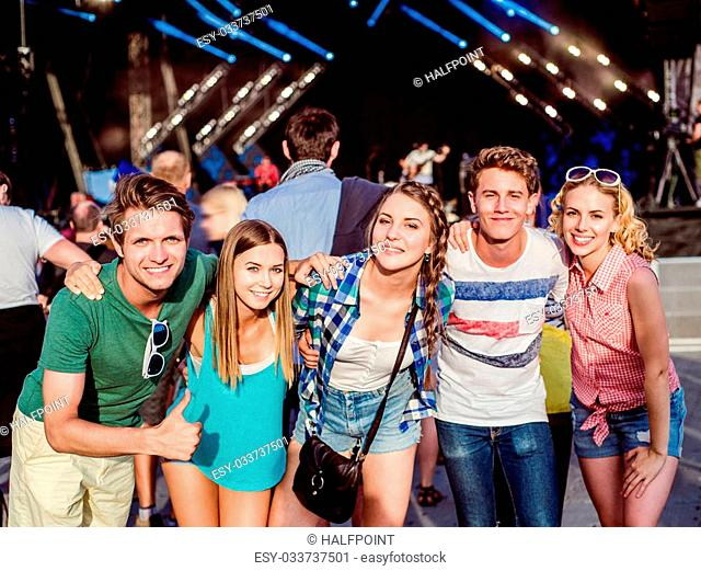 Teenagers at summer music festival against the stage in a crowd enjoying themselves, having fun