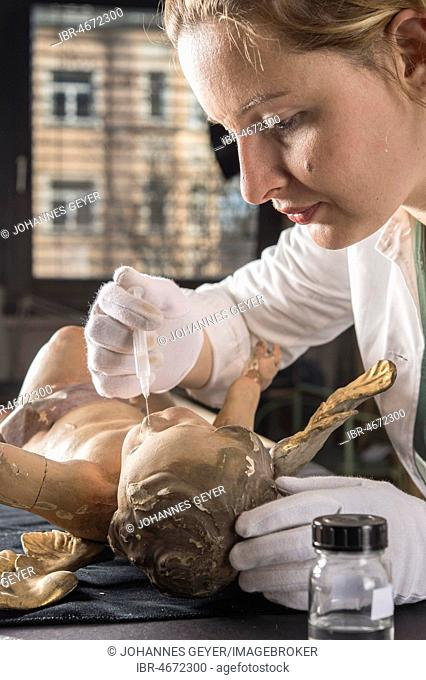 Restoration studio, restorer, woman holding syringe with fish glue on angel face, for fixing the filling material, Munich, Bavaria, Germany