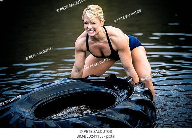 Caucasian woman lifting heavy tire in lake