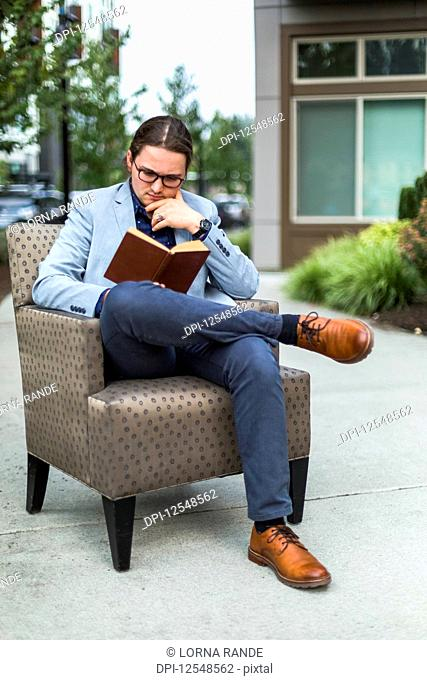 A young man sits reading a book in an armchair on an outdoor patio; Bothell, Washington, United States of America