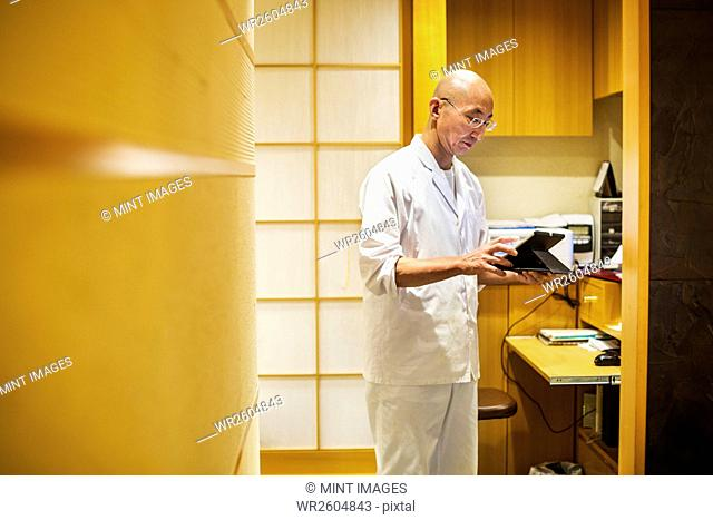 A chef in a small commercial kitchen, an itamae or master chef using a digital tablet