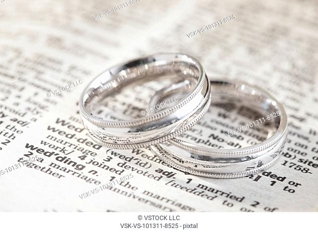 Close-up of silver wedding rings on dictionary page with wedding definition