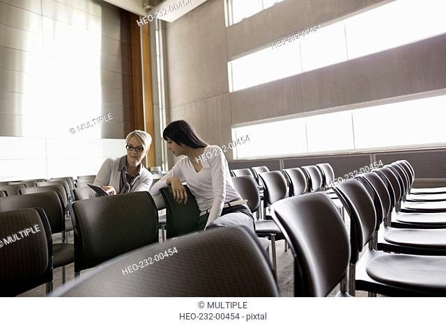 Women using digital tablet in auditorium