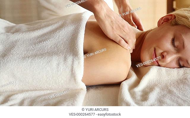 Gorgeous young woman smiling while receiving a back massage at spa