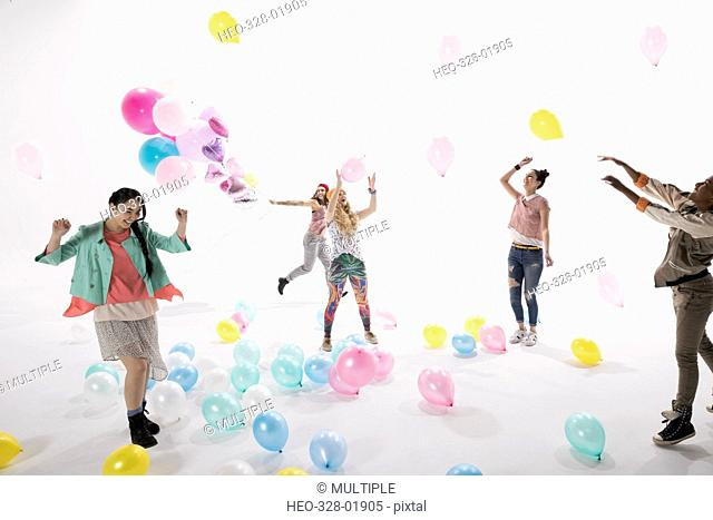 Women friends playing with multicolor balloons against white background