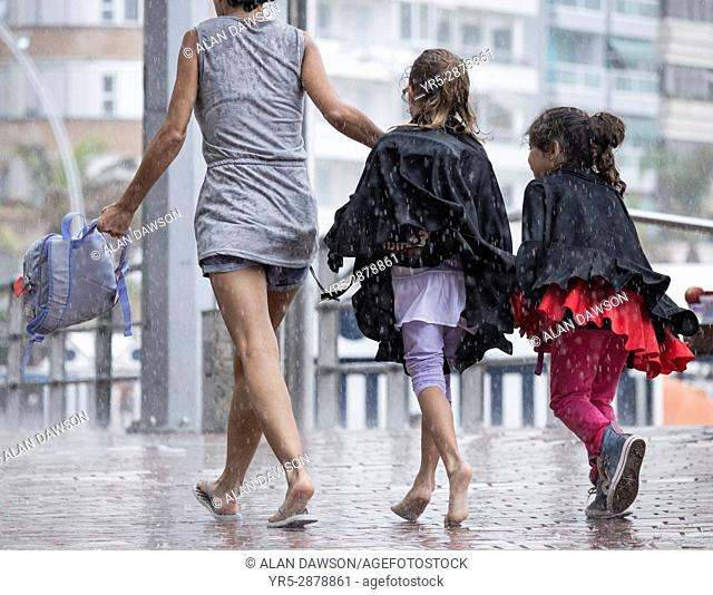 Las Palmas, Gran Canaria, Canary Islands, Spain. People leaving Las Canteras beach as heavy rain falls as a storm passes over the city