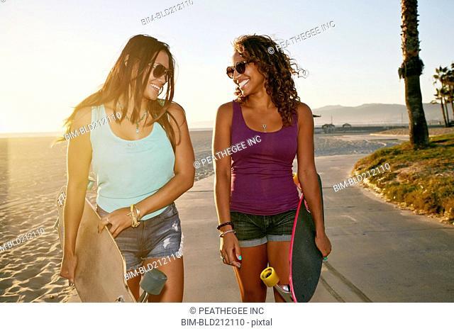 Women carrying longboards on beach