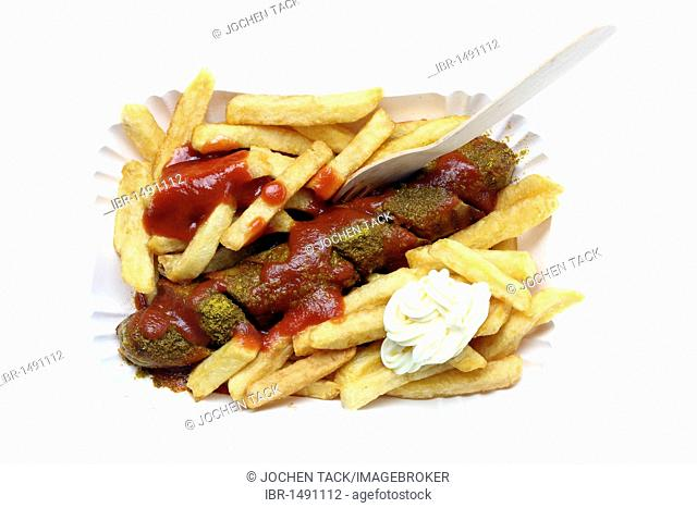 Currywurst with chips, mayonnaise and curry sauce on a paper plate, hot pork sausage