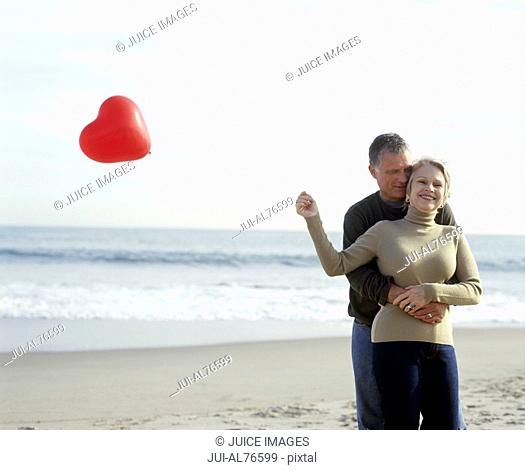 View of a middle aged man embracing his wife as she holds a heart-shaped balloon