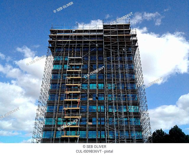 Low angle view of office building surrounded in scaffolding