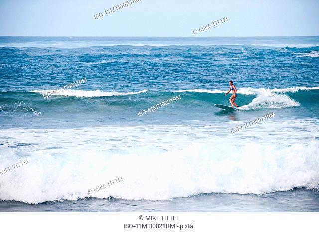 Surfer riding rocky waves