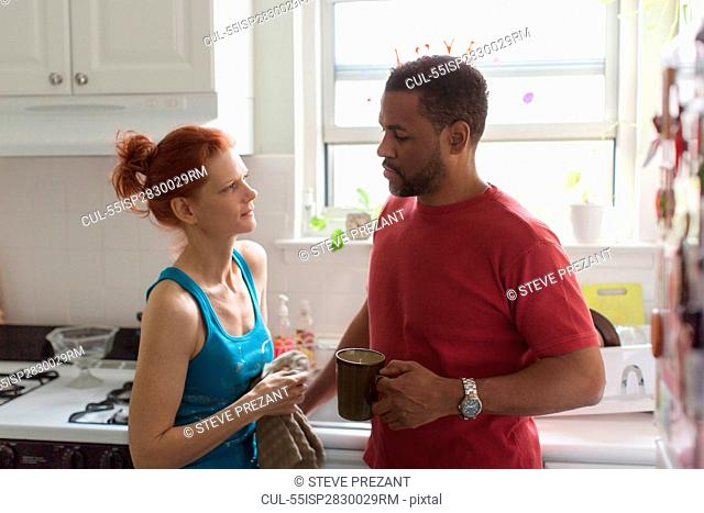 Mature couple in kitchen, man with coffee