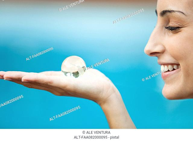Young woman holding crystal globe in palm, side view
