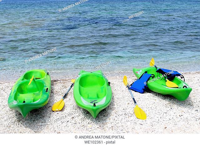 Three green kayaks on beach Capo Bianco Isola d'Elba Tuscany Italy