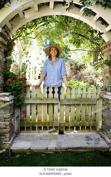Mature woman standing under garden arch, portrait