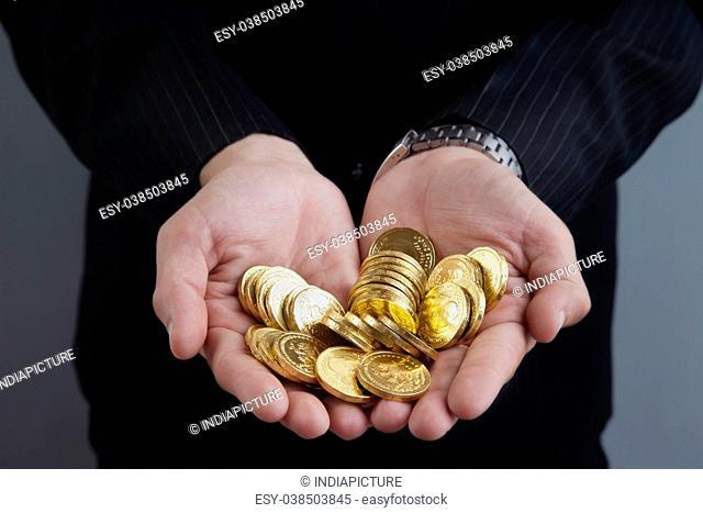 Businessman's hands holding coins, closeup shot