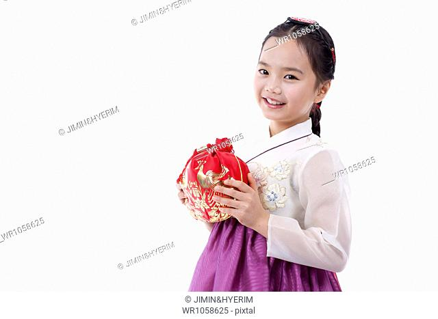 a girl in Korean traditional costume holding a luck bag