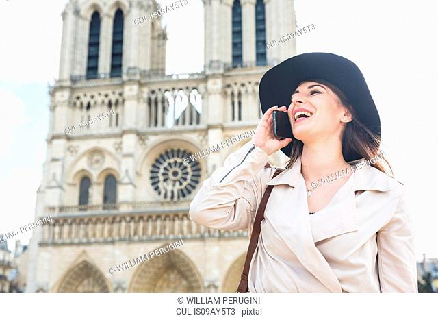 Young woman talking on smartphone at Notre Dame, Paris, France