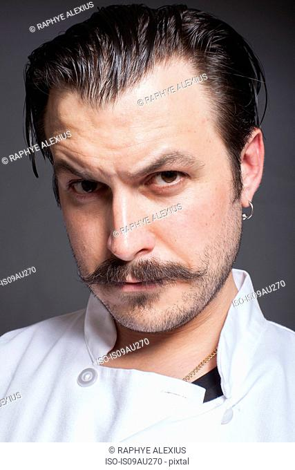 Close up studio portrait of mid adult male chef with raised eyebrow