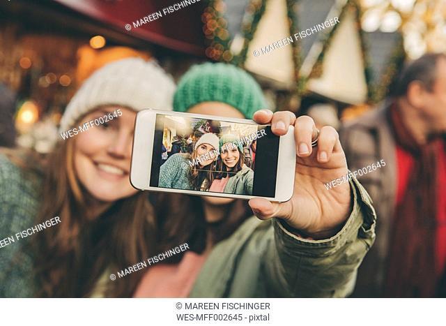 Two happy women taking a selfie on the Christmas Market