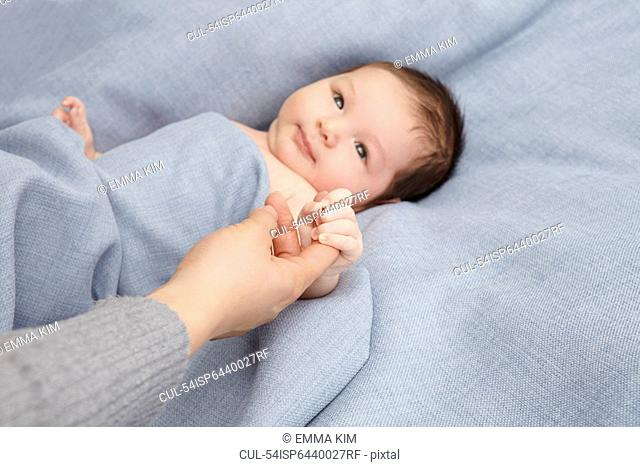 Baby boy holding mothers finger in bed