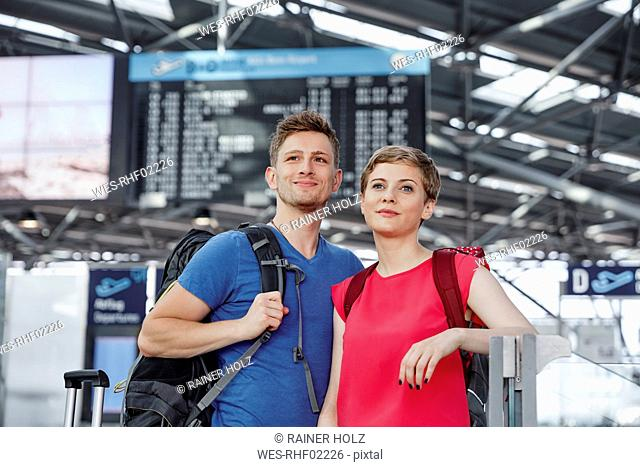 Smiling couple at arrival departure board at the airport