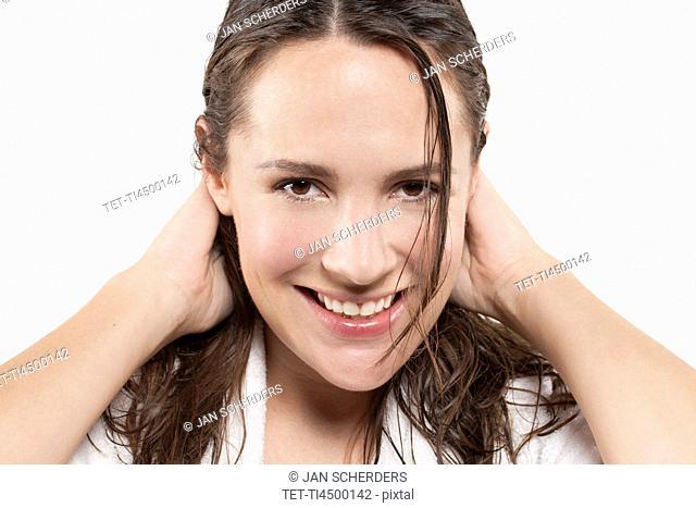Portrait of woman with long wet hair, studio shot