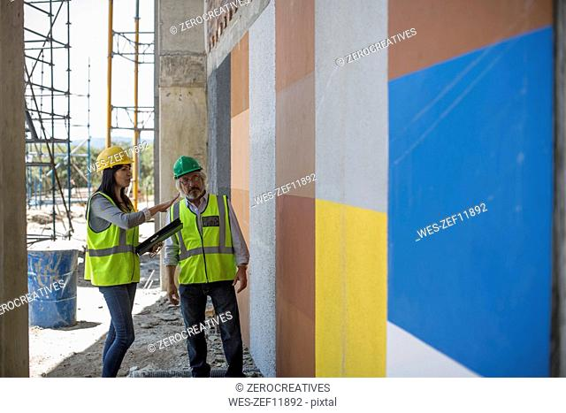 Engineer inspecting construction site, talking to workers