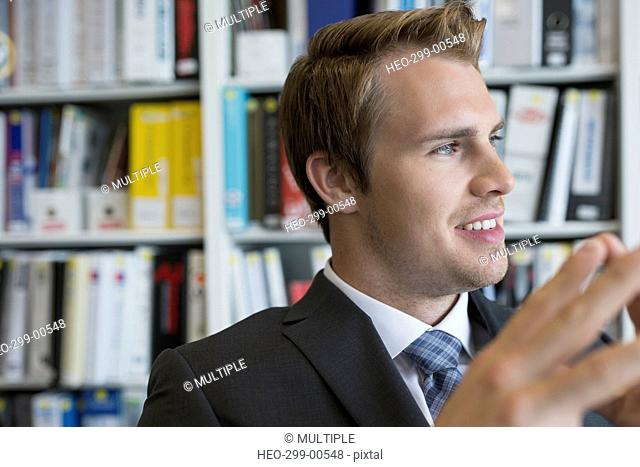 Smiling businessman looking away in library