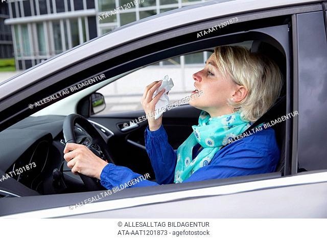 Female car driver is sneezing